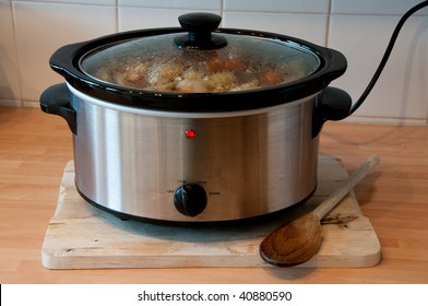 Slow cooker with wooden spoon on chopping board cheep winter cooking