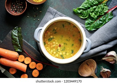 Slow cooking soup with curry, chickpeas, beans and chard. The concept of autumn or winter food