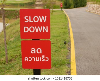 Slow Down sign on bike lane with English and Thai spelling.English translate;Slow down.
