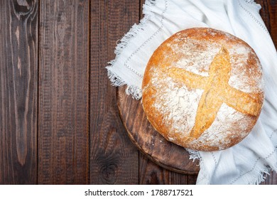 Slow fermentation no knead Classic Boule bread, round loaf on a wooden board with a white cloth, horizontal, top view, copy space