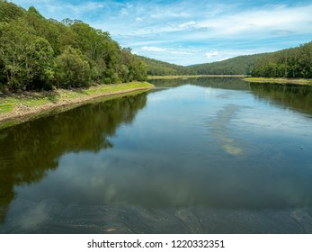 Slow flowing river meanders through riverbanks populated with trees. Wilderness area captured on sunny day and features dramatic sky. Environmental conservation and protecting vital water resources.