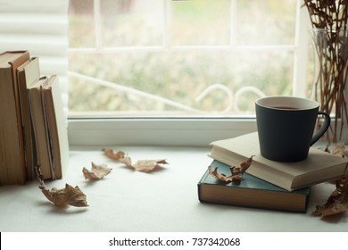 Slow living, digital detox, Warm and comfy autumn concept. Book, cup of tea and candlestick on window sill in house. Reading and relaxing in cold weather at home. Quiet silent homely scene.