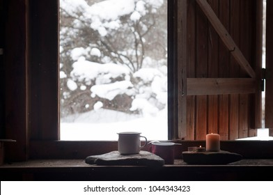 Slow morning in the mountain cabin house.Two coffee mugs and candles in the window frame. Snowy winter landscape with falling snow in the background. Romantic sunday morning. Leisure time concept.