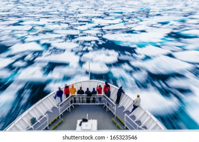 Slow motion blur of people standing on the bow of a ship while moving through an ice field.