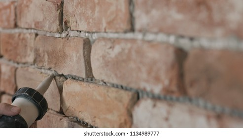 Slow motion closeup of worker filling seam between bricks with mortar from sealant gun