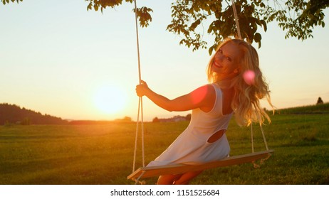 SLOW MOTION LENS FLARE: Smiling young woman swaying on rope swing under big tree at sunrise. Pretty girl in white dress swinging over the sun at golden sunset. Beautiful lady enjoying summer evening