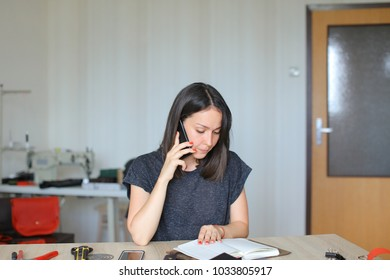 Slow motion needlewoman speaking on smartphone, seamstress discussing wholesale trade of leather products with partner using mobile. Young woman sitting near table with notebooks bags wallets