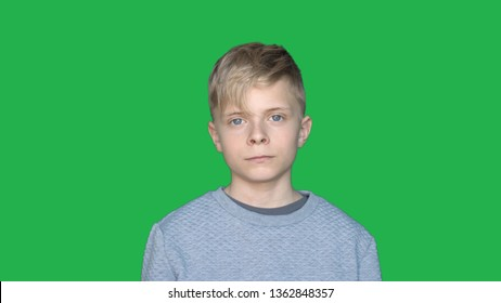 In slow motion on the background of a chromakey, a young guy (boy) shows different emotions. Concept of: Green background, Chroma Key, Real feelings, Fighter, Like, Fashion, Blonde.