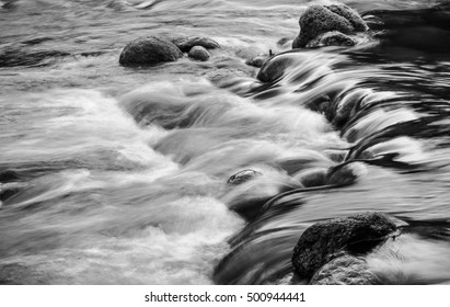 Slow motion river stream flowing among stones at Sungai Sedim Kulim, Kedah, Malaysia. Image in black & white and noise, grain effect.