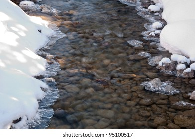 A slow moving shallow creek with untouched snow and ice along its banks