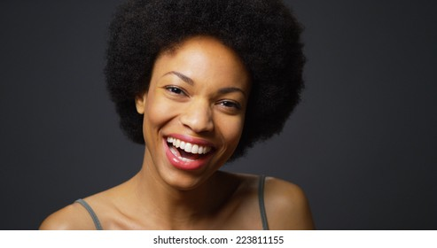 Slow pan up African woman laughing and smiling