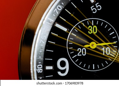 Slow shutter macro photo of an analog wristwatch with its chronograph seconds indicator moving on a red background.