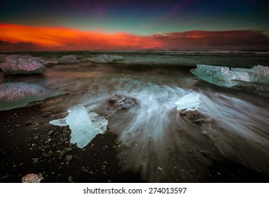 Slow shutter photo showing wave movements around Ice blocks that get washed ashore at black sand beach in Iceland during sunset.