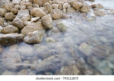A slow shutter speed captures clear sea water washing over rocks. ghosting water calming effect.