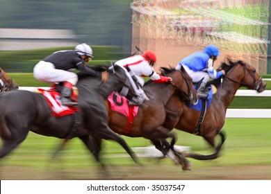 Slow shutter speed rendering of three racing jockeys and thoroughbreds