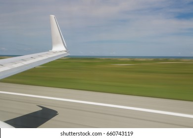 Slow shutter view from inside of plane taking off showing wing tip