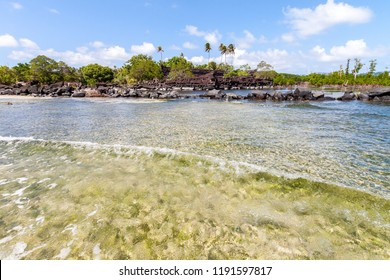 Slow wave in coral and sand shallow lagoon of Pohnpei island, Micronesia, Oceania with Nan Madol prehistoric ruined stone city built of giant basalt slabs, overgrown with palms, in the background.