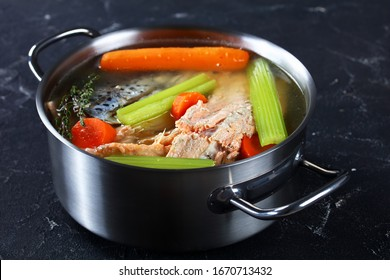 slow-cooked fish broth or soup of salmon, onion, carrot, celery, herbs and spices in a stockpot on a concrete table, horizontal view from above, close-up