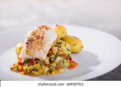 Slowly roasted cod with white chili roasted potatoes with herbs and vegetable salad pepper cucumber tomato and onion cut into small pieces