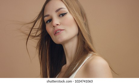 slowmotion closeup of model in studio with blowing hair turning and watching aside. Beige tonality of clip. Studio light