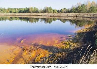 Sludge accumulator. Oil sludge on the water surface and at the shore.