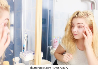Sluggish woman looking at her skin condition in bathroom mirror. Sleepy languid female feeling tired, examing dark circles bags under eyes and wrinkles.