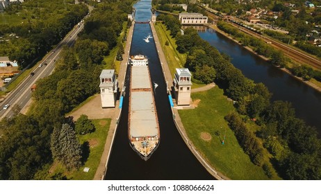 Sluice Gates on the River. Aerial view barge, ship in the river gateway. River sluice construction, water river gateway. Shipping channel.