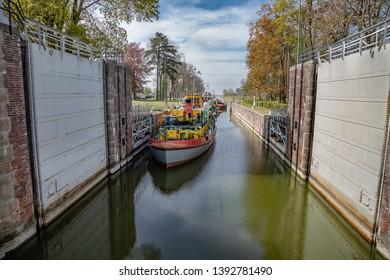 "Sluice, water gate with colorful tugboats parked along the berth in Sobieszewo-city in Poland, connecting canal of main stream of ""Wisla"" river with ""Martwa Wisla"" (river)."
