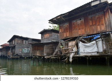 Slum houses on the river in Bangkok. Abandoned houses oncanal full of mud and rubbish. January 2019