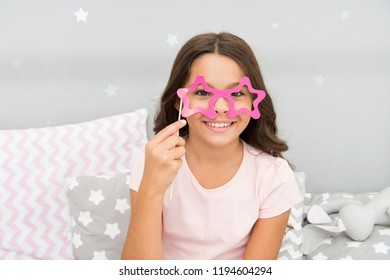 Slumber party photo booth props. Kid girl cheerful posing with star shaped eyeglasses party attribute. Prepare photo booth props hand made or buy for party. Printable photo booth props pajama party.