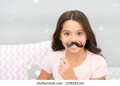 Slumber party photo booth props. Kid girl cheerful posing with black mustache party attribute. Prepare photo booth props hand made or buy for party. Printable photo booth props pajama party.