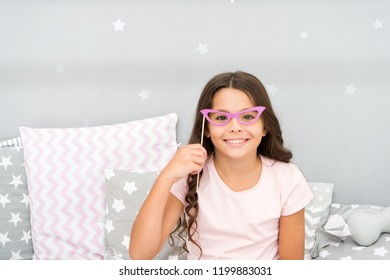 Slumber party photo booth props. Kid girl cheerful posing with retro pink eyeglasses party attribute. Prepare photo booth props hand made or buy for party. Printable photo booth props pajama party.