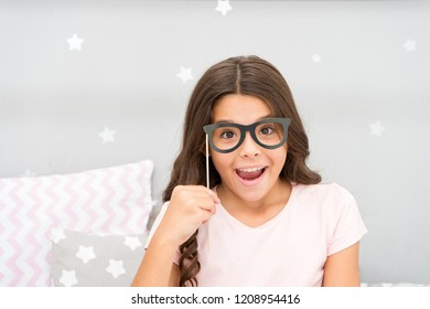 Slumber party photo booth props. Kid girl cheerful posing with vintage black eyeglasses party attribute. Prepare photo booth props hand made or buy for party.