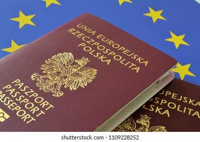 SLUPSK, POLAND – 01 MAY 2018 Passports on the background of the EU flag. Subtitles in Polish