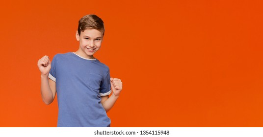 Sly boy making silly grimace, thinking about joke, orange panorama background with empty space