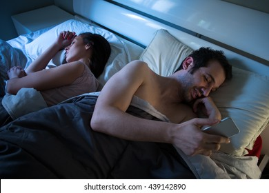 Sly boyfriend using mobile in bed while his girlfriend is sleeping