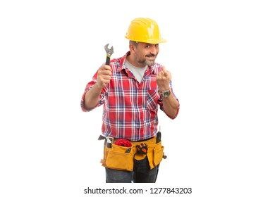 Sly constructor smiling with wrench held up and making come here gesture with index finger isolated on white background