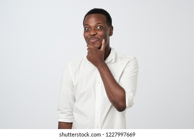 Sly cunning african man touching chin with finger and looking away. Handsome guy thinking.