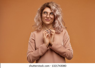 Sly hipster girl planning prank or evil trick, clasping hands and smiling mysteriously. Pensive cunning young woman in eyewear having tricky plan in mind, posing isolated at blank orange studio wall