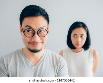 Sly husband with tricky funny face and wife with suspicious face.