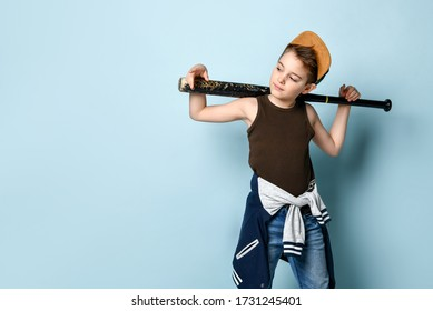 Sly little bubby stands near the wall looking aside holding baseball bat on his shoulders. Childhood, naughty, troublemaker. Three quarter length portrait isolated on blue background. Copy space