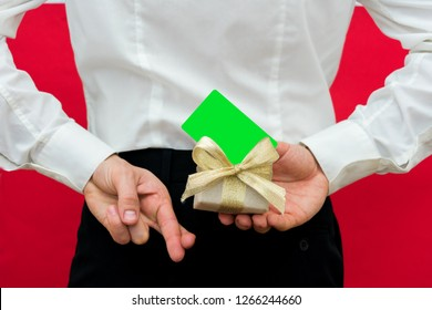 Sly man crossing his fingers behind his back, guy in white shirt is holding a gift box with a gold ribbon and businesses card, with copy space, for dvertisement, for records or a slogan, front view