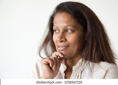 Sly mix raced woman thinking over idea. Pensive mid adult lady touching chin and looking at copy space away. Thinking concept