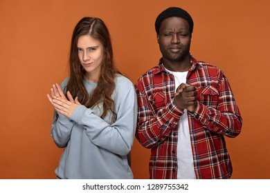 Sly mysterious young woman of Caucasian appearance and her cunning dark skinned boyfriend going to make fun or prank their common friend, squinting eyes and rubbing hands, scheming tricky plan