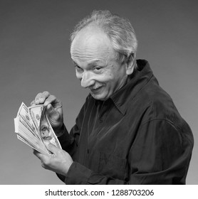Sly old man with dollars on a grey background
