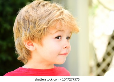 Sly playful baby boy. Funny child with cute hairstyle. Smart kid with idea, sly look. Children face.