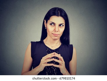 Sly, scheming woman plotting something isolated on gray background. Negative human emotions, feelings, attitude