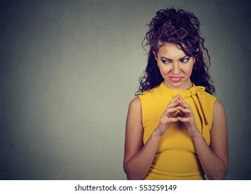 Sly, scheming young woman plotting something looking sideways isolated on gray background with copy space. Negative human emotions, feelings, attitude