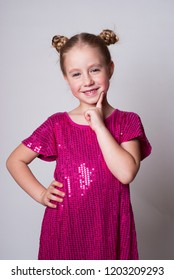 Sly Smiling cute girl in а pink sparling dress