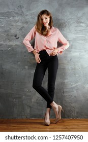 Sly, tricky caucasian girl standing near the wall with hands in pocket